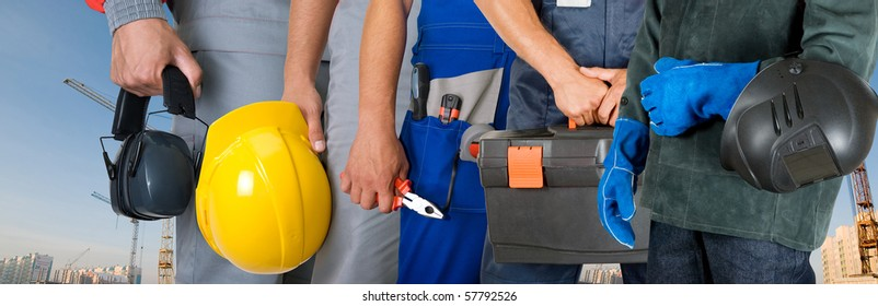 workers closeup with equipment on building background