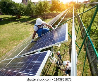 Workers command mounting solar panels on house's roof. Innovative high-tech exterior solution. Environment friendly,resources saving, using renewable solar electricity. Warm, sunny weather.