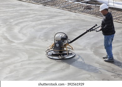 Workers at the construction site of the foundation of the building , grinding concrete floor .Belarus, Minsk, October 22, 2014