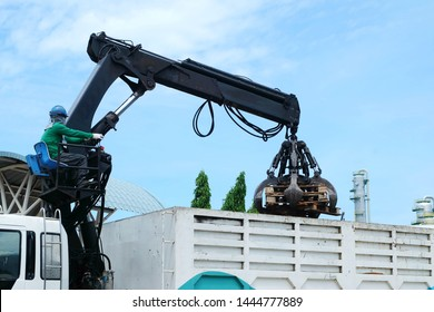Workers are controlling machine loader manipulator with hydraulic multi valve crab bucket or crane garbage truck uploads industry waste this is pallets wood to transport for recycle.