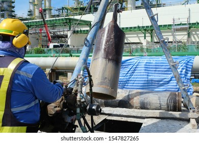 Workers are controlling the tripod rig machine is drilling holes in the construction site for concrete bored piles work and reinforced elements cast into drilled holes to be the foundation.