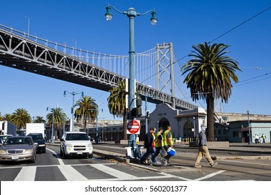 Workers crossing street in San Francisco under Oakland Bridge