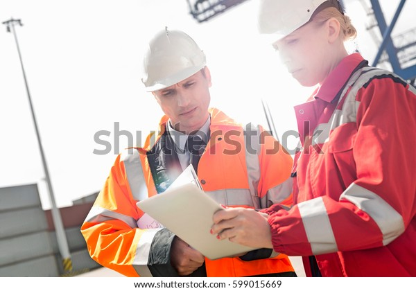 Workers discussing over tablet computer in shipping yard