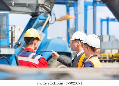 Workers discussing in shipping yard