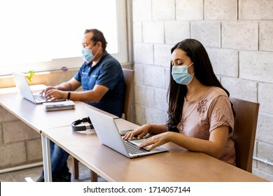 Workers doing office work on computers with social distance and face masks in times of the COVID-19 pandemic.
