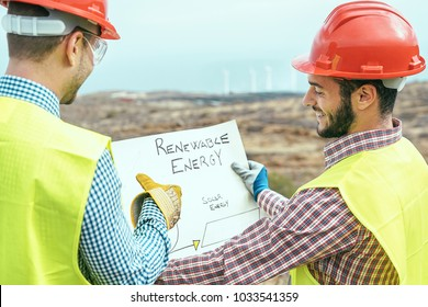 Workers engineers reading and talking about the new renewable energy project - Two builders discussing how to build windmill and panels solar - Construction, environment, saving nature concept