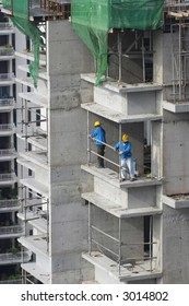 Workers erecting a safety barrier at a construction site for high-rise residential apartment block