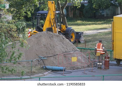 Workers excavate the pit with an excavator. Road repair. Pipeline failure.