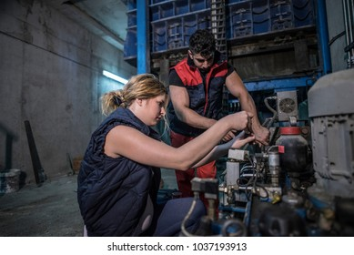 Workers in factory looking and repainring industrial engine in factory warehouse