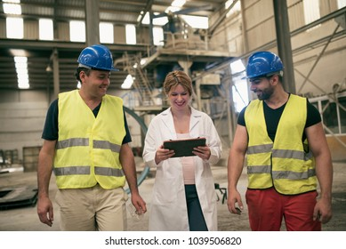 Workers in factory walking and looking table. Two men with helmet and scientist pregnant woman.