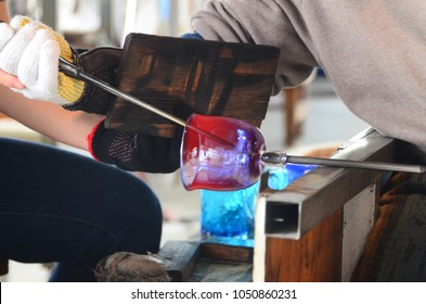 Workers are forming a hot glass at Ryukyu Glass Village, Tourist attraction for glass factory in Okinawa Japan.