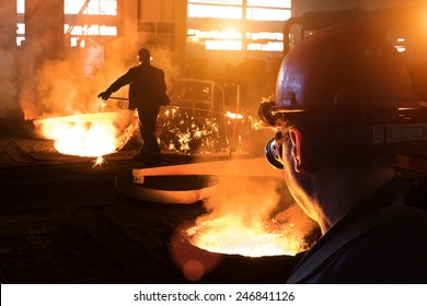 Workers in a foundry, molten steel and metal