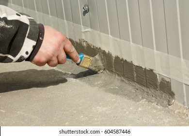 Workers hand applying a memory shape polymer waterproofing sealant with a brush to the outer wall-floor connection of an industrial building