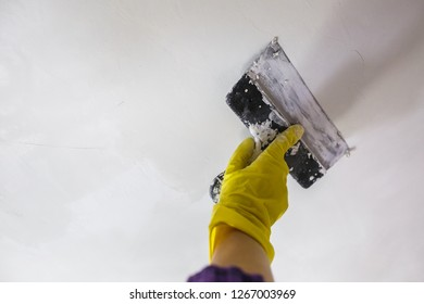 worker's hand in yellow gloves holding putty knife patching a hole with spatula with plaster or putty in white wall. Renovation and repair process, remodeling interior of room at apartment building