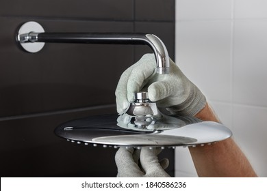 The worker's hands install the head of the built-in shower faucet.