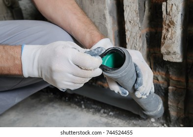 Worker's hands are installing sewer pipes in a kitchen of a apartment.