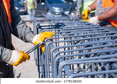 workers hands using iron wire for securing iron bars with wire rod for reinforcement iron reinforcement in the construction site