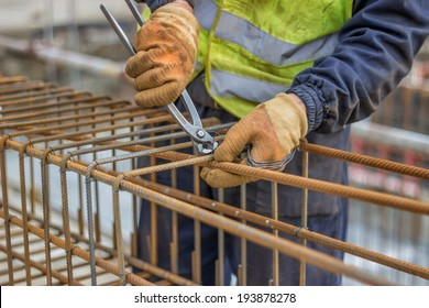workers hands using steel wire and pincers to secure rebar before concrete is poured over it. Selective focus on center portion of image.