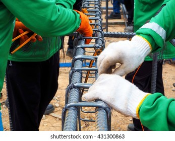 workers hands using steel wire and pincers to secure rebar before concrete is poured over it.