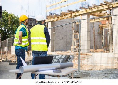 Workers in hardhat and green jacket posing on building site
