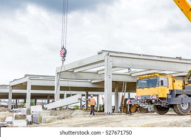 Workers are helping mobile crane to carry concrete joist for assembly huge construction.