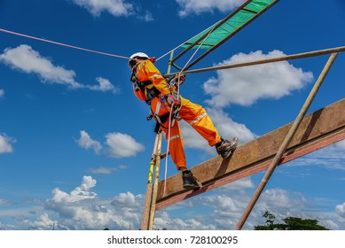 workers up high with safety equipment and safety belts, construction workers wearing safety harness belt high place on blue sky background