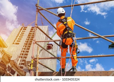 workers up high with safety harness, safety equipment and safety belts on scaffolding on city building on background