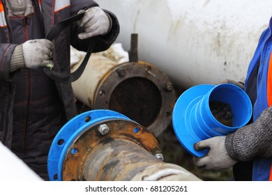 Workers install a cured-in-place pipe (CIPP) renewal systems. One worker prepares a cushion gum, another one holds a pipe fitting part