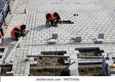 Workers install paving slabs in the courtyard (paving)