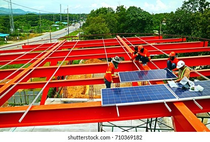 the workers install the solar panels on top of red steel structure to generate electricity from sunlight so impressive pattern for technology background