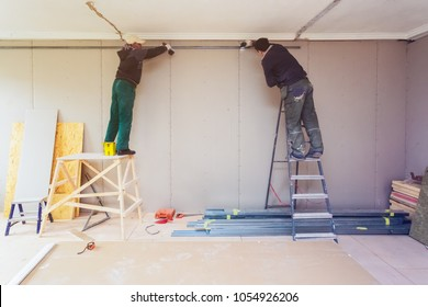Workers are installing plasterboard drywall for gypsum walls in apartment is under construction, remodeling, renovation, extension, restoration and reconstruction.