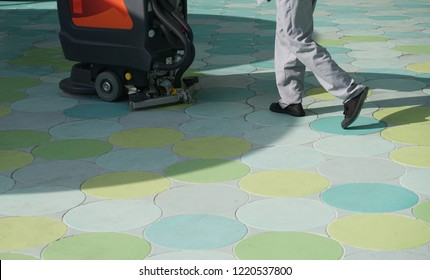 Worker's legs using scrubber drier machine for cleaning pavement tile, Cleaning floor with electric cleaner
