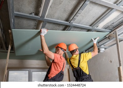 Workers are lifting plasterboard for further attaching to the ceiling.