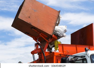 Workers load garbage from the tank in a specialized car garbage truck. A specialized car removes garbage.