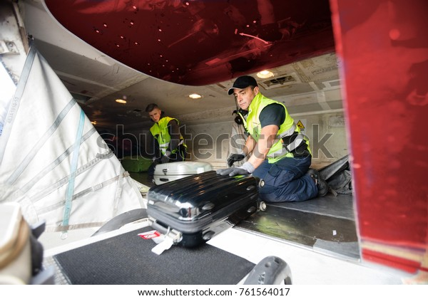 Workers Loading Luggage In Airplane