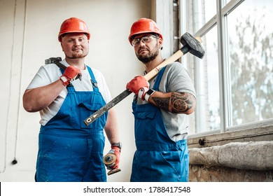 Workers, looking at the camera, standing at the construction site. They are wearing red safety helmets and one of them is holding a sledgehammer for repairs.