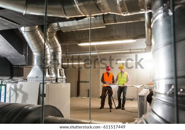 Arbeiter, die das HVAC-System endgültig berühren. HVAC-System steht für Heizungs-, Lüftungs- und Klimaanlagen. Teamarbeit, HVAC, Innenraumkomfort-Konzeptfoto.
