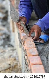 Workers masonry Clay brick to wall.