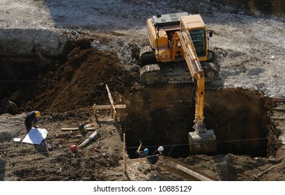 workers and  mechanical shovel. in building site