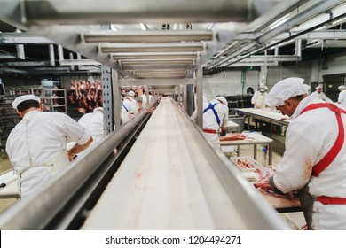 Workers at meet industry handle meat organizing packing shipping loading at meat factory.