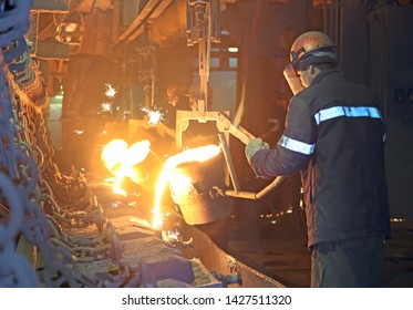 Workers at a metallurgical plant pour hot metal, cast iron, copper in the form of products.