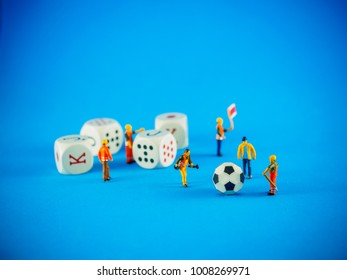 Workers miniature figures surrounded by gambling elements: dices and a soccer ball