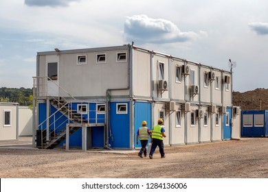 Workers at mobile containers and cabins base for the site manager and employees. Construction site work site fast build mobile prefabricated container houses.