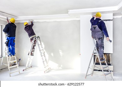 Workers mount suspended ceilings from plasterboard