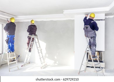 Workers mount suspended ceilings from plasterboard.