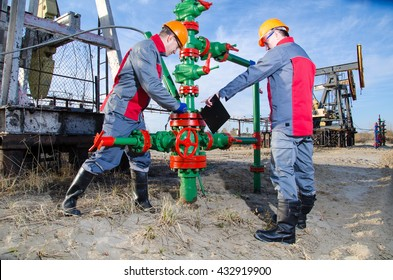 Workers in the oilfield, one repairing wellhead with the wrench, other supervising. Pump jack and wellhead background. Oil and gas concept.