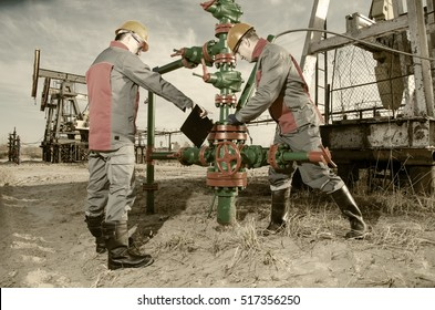 Workers in the oilfield, one repairing wellhead with the wrench, other supervising. Pump jack and wellhead background. Oil and gas concept. Toned.