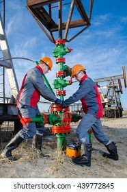 Workers in the oilfield repairing wellhead with the wrench. Pump jack and wellhead background. Oil and gas concept.
