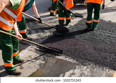 Workers on Asphalting paver machine during Road street repairing works. Street resurfacing. Fresh asphalt construction. Bad road