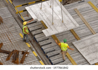 Workers on a construction site gettiing the concrete slab directed by a big crane